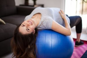 Pretty Hispanic pregnant woman using a stability ball at home for exercising during pregnancy