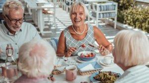 kaksi iäkkäämpää paria syövät terveellisen päivällisen hyväntuulisina